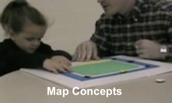 kindergarten student exploring a tactile store map with an O&M