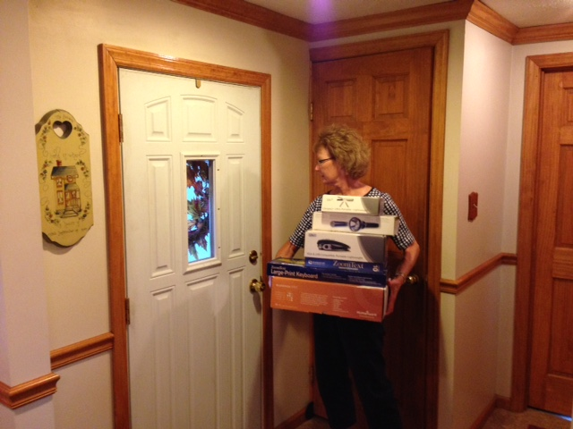 A woman carries boxes to the front door.