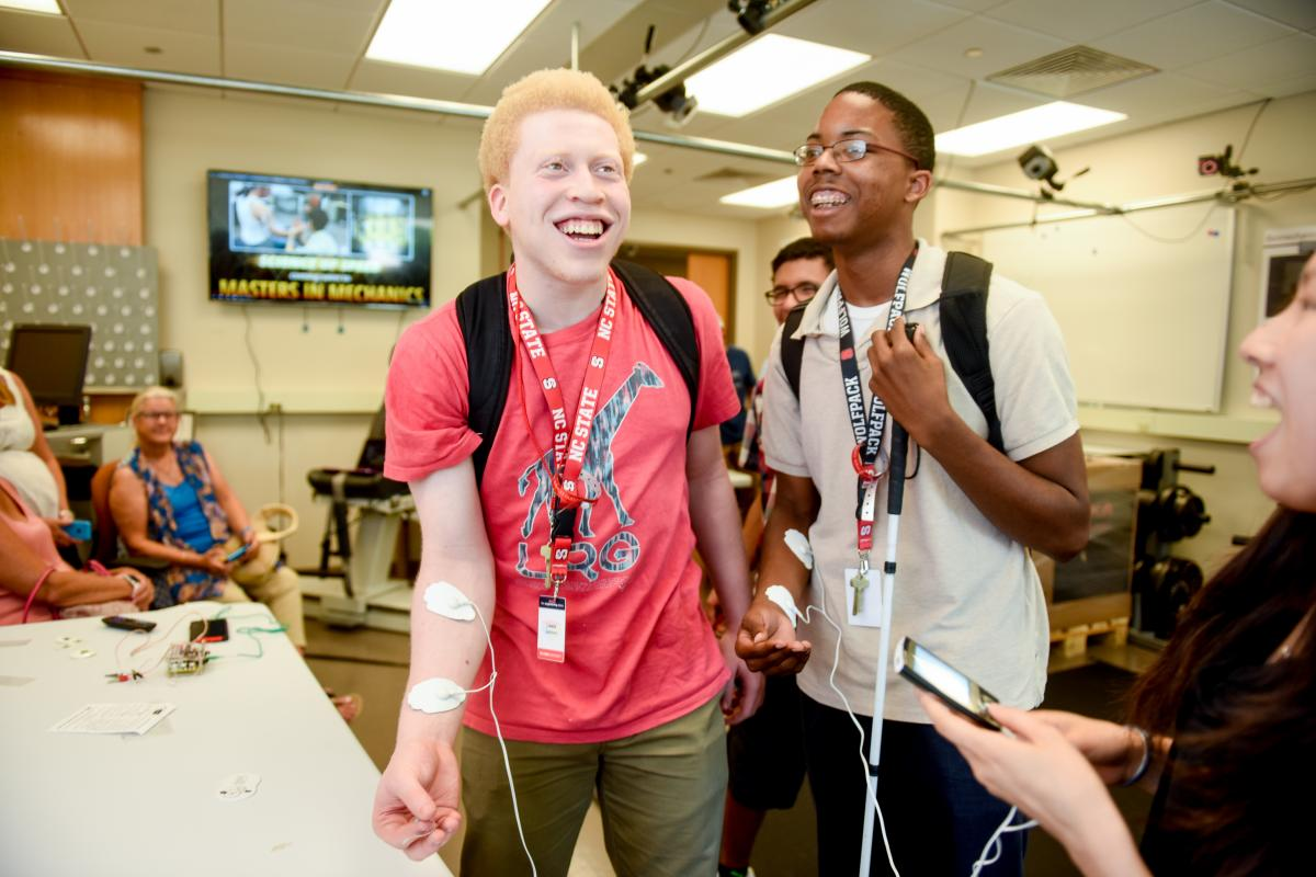 Two campers with smiling and pained expressions as their arm muscles are stimulated through electrodes.