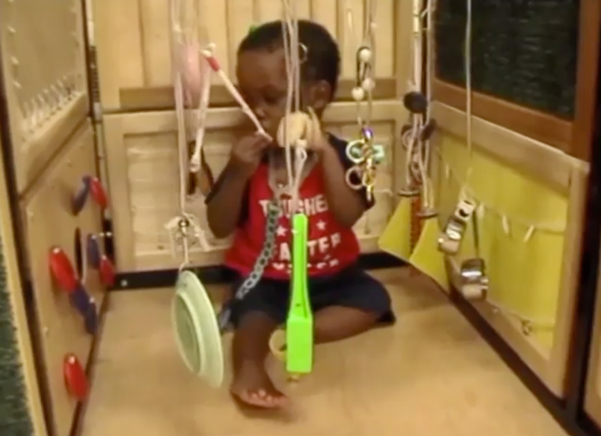 A child sitting in a Little Room puts a toothbrush near his mouth