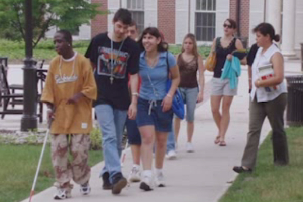 A group of students walking across a college campus.