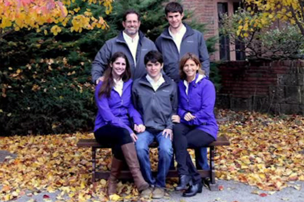 Photo of the Brint family with teen-aged Alan sits between his mother and sister on a bench.