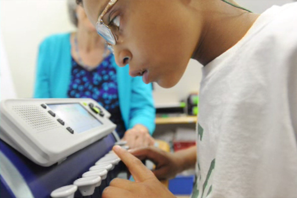 A boy who is visually impaired peering closely at the screen of his Perkins Smart Brailler.