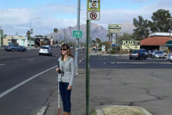 A high school aged girl standing on the sidewalk, holds mobility cane as she waits for the bus.