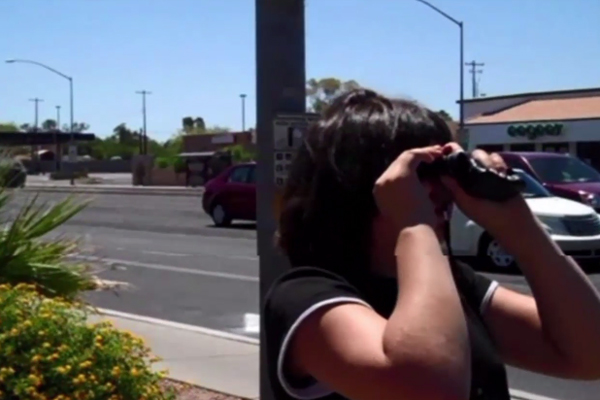 A young woman using a monocular to identify the cross street of an intersection that she has traveled to.