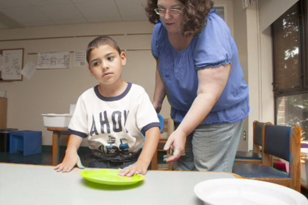 A young boy who is blind is being taught how to set the table for lunch.