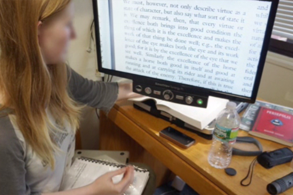 A visually impaired woman sitting at her dorm and reading with the assistance of a screen reader.