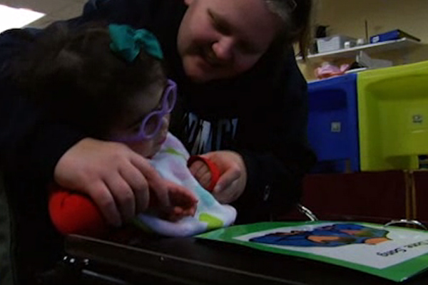 Savannah in her preschool classroom with an aide leans towards her.