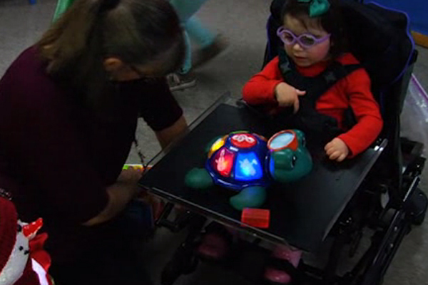Savannah plays with a toy turtle that has various raised panels on its shell that light up and play sounds when pushed.