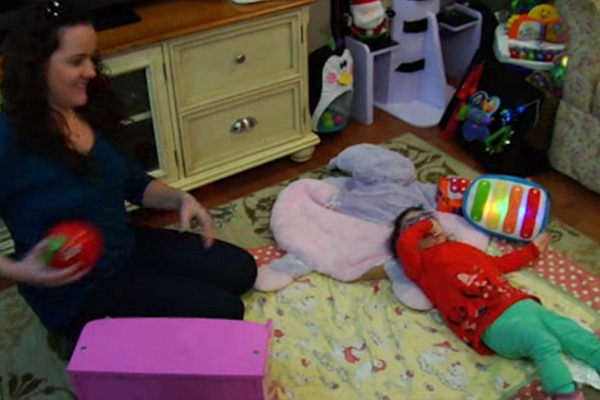 Savannah, Lacey's daughter is lying on a blanket on the floor at home with a musical toy that lights up.