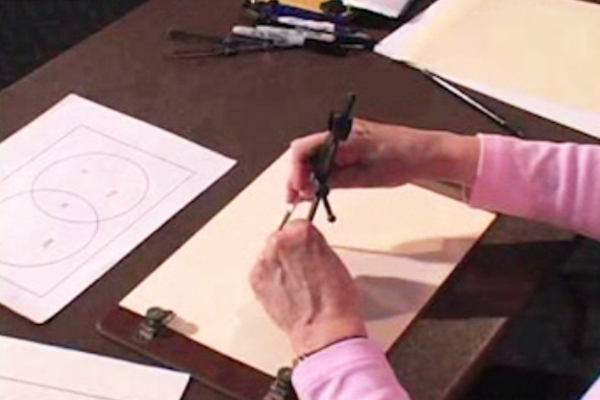 A person is using a Howe Press compass to trace and produce raised-line drawings on a sheet of braille paper.