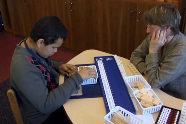 A boy who is blind is working on fractions using segments of woods in various sizes.
