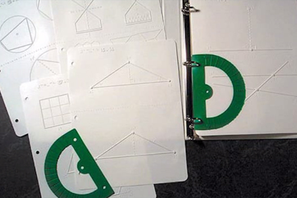 Photo of several thermoform pages depicting a variety of geometric shapes, as well as a page with plot points of intersecting lines.