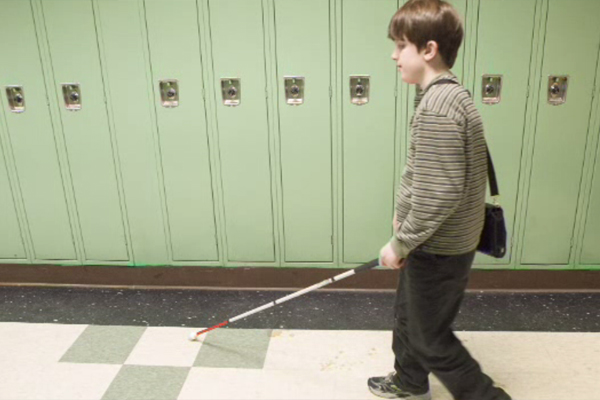 An adolescent boy who is blind navigating the hallway of his public school.