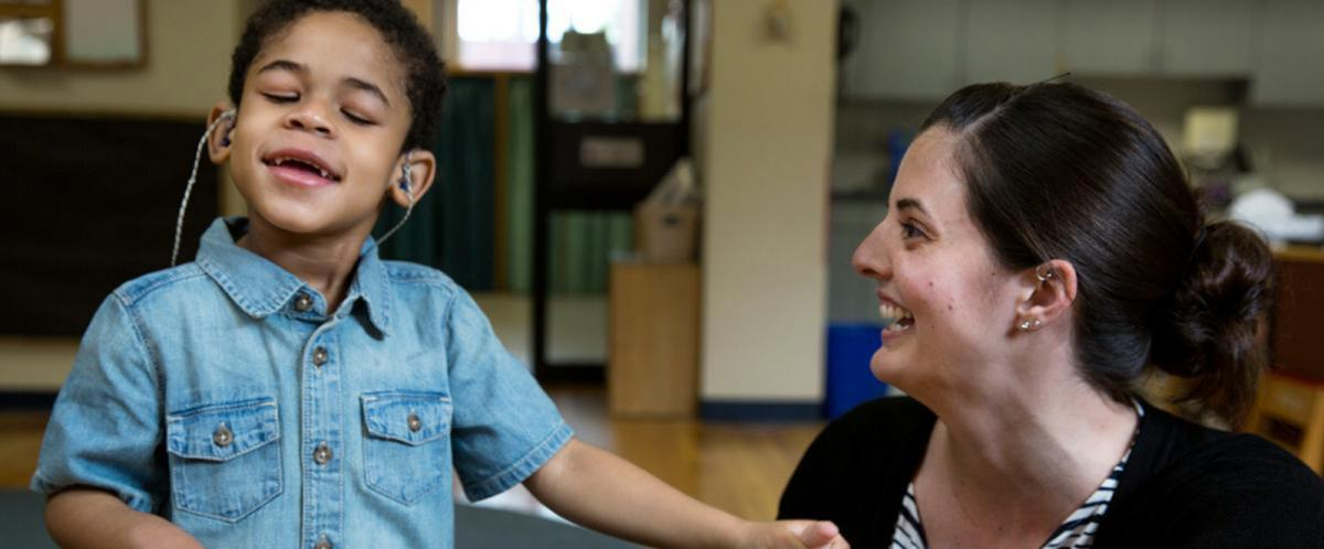 A deafblind boy listens happily and an instructor teaches