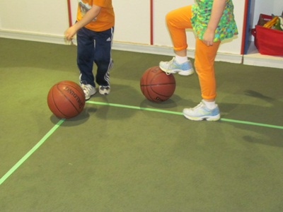 Two preschoolers running with ball and stopping the ball.