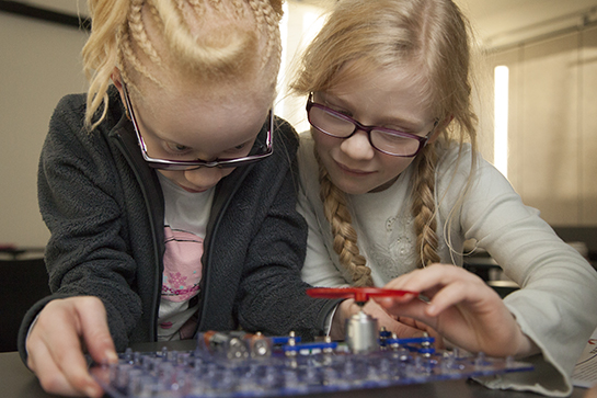 Two young girls work on a robot.
