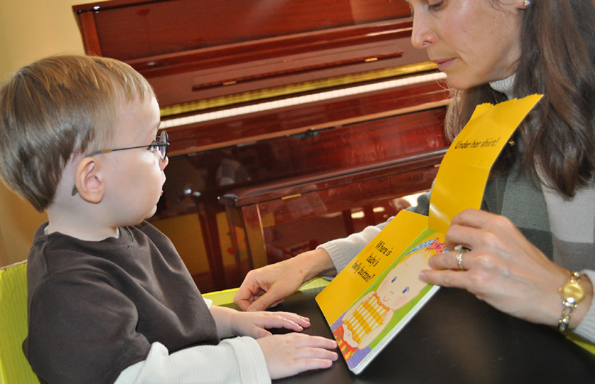 A teacher shows a child who is blind a kids book