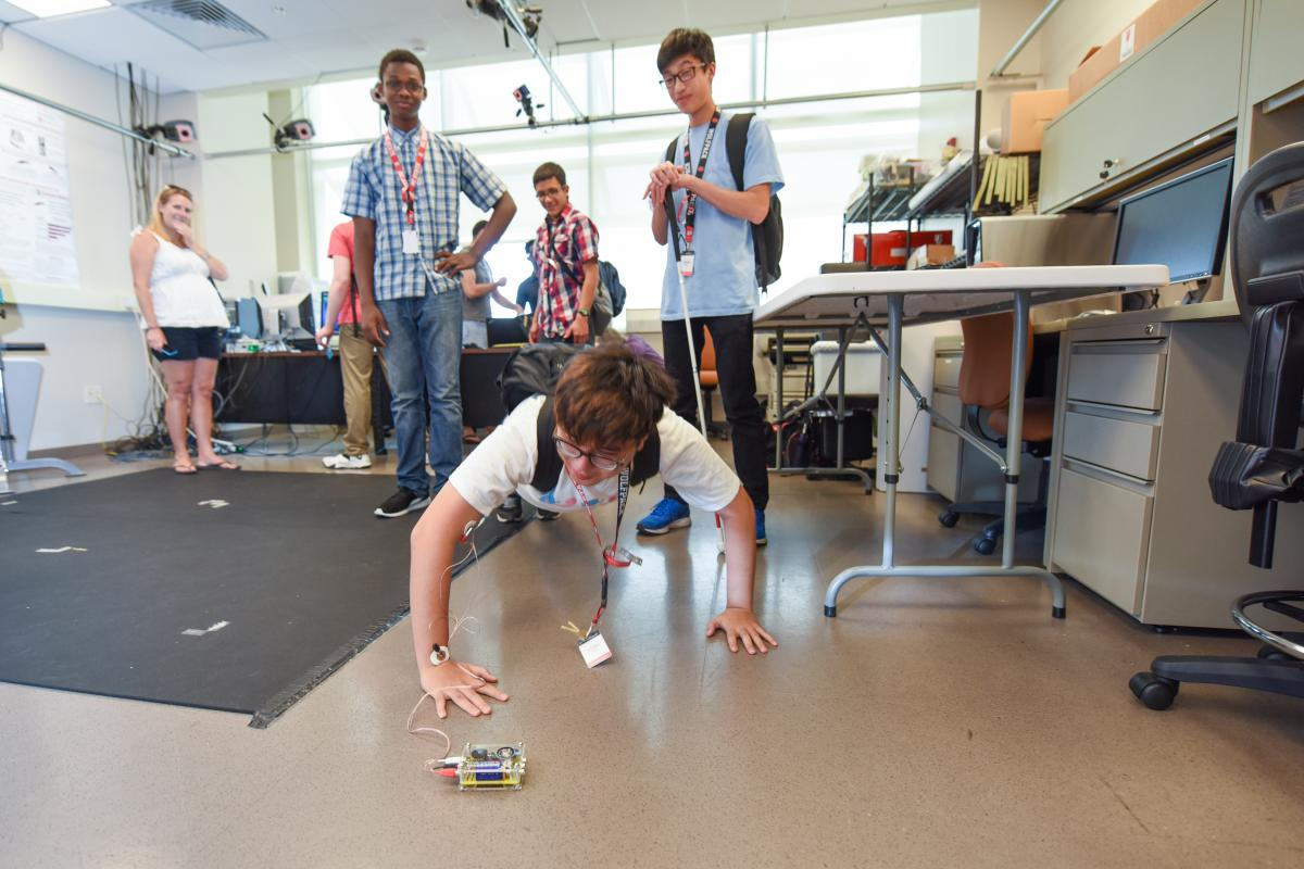 Camper doing push ups to create muscle energy; voltmeter uses buzzes and lights to indicate energy levels.