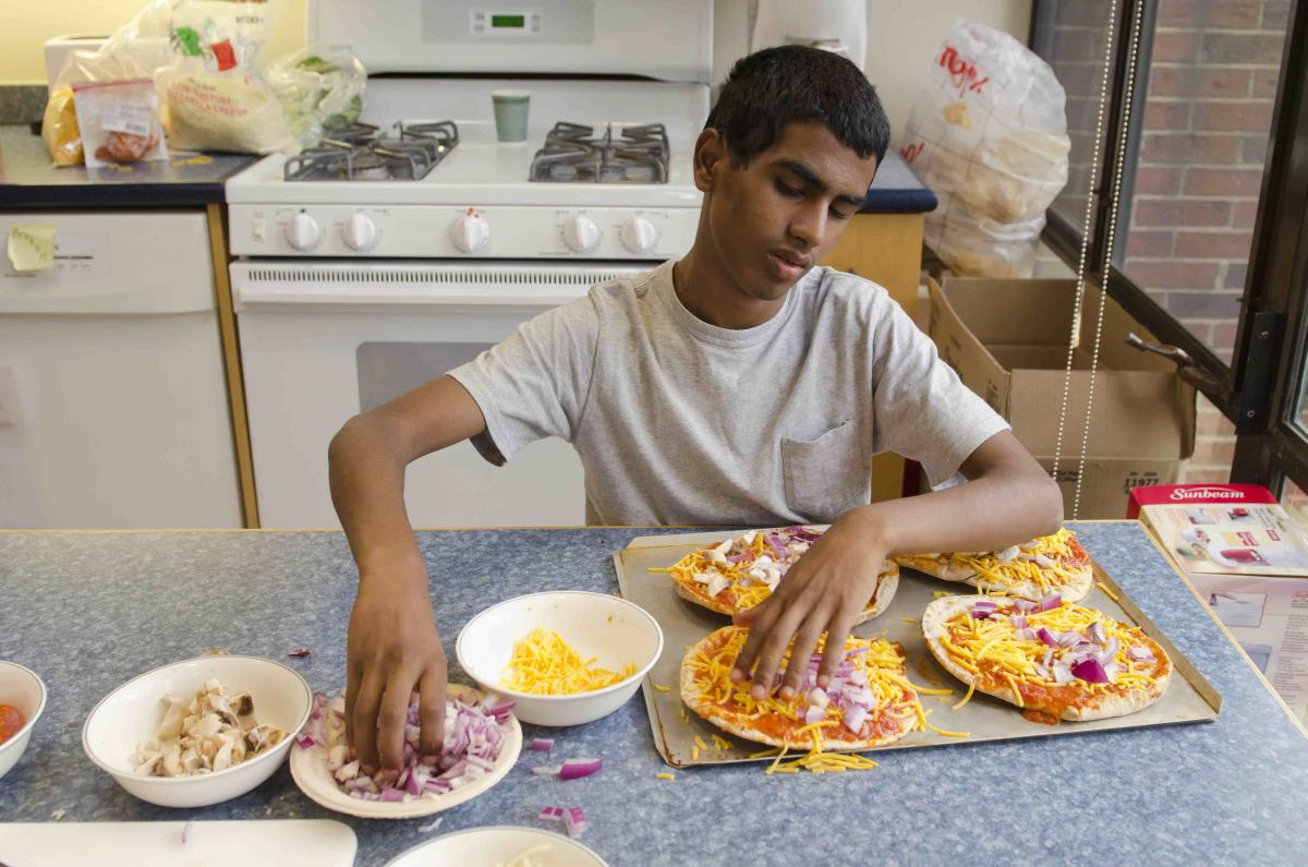 A boy puts onions on his pizza