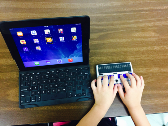 Preschooler's hands typing on a Braille Display with an iPad and Bluetooth keyboard beside her.