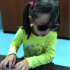 Young girl with pig-tails intently pressing a chord command on her braille display.