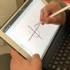 Photo of iPad displaying PDF Expert's graph paper and student using Apple Pen to draw a parabola.