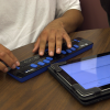 MAP field test: High school student's fingers are on a Braille Focus paired to an iPad displaying a math graphing question.