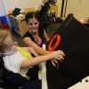 Student touches an tactille object on a black board.