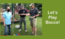 Image of 3 men standing by red, yellow and blue Bocce balls.