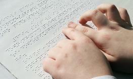 A person reading braille with their fingers.