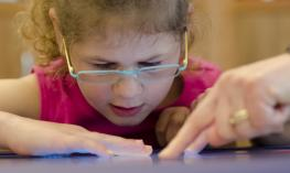 A young girl wearing glasses is pointing at a computer screen.
