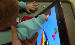 Young child using an iPad on a stand with support at the elbow