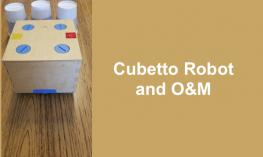 "Cubetto Robot (big block on wheels) on a route to go around an obstacle (3 cups) with text, ""Cubetto Robot and O&M"""