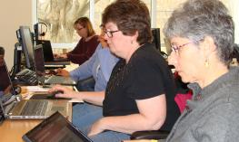 A group of workshop participants looking for materials on their laptop.