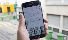 Photo of a hand holding a smartphone displaying the Desmos graphing calculator app.