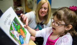 A teacher and a visually impaired student read a book.