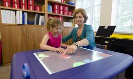 A young girl wearing glasses is moves an object on the table with her teacher.