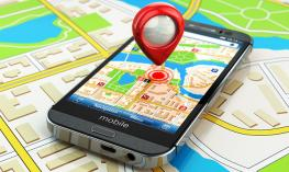 A smart phone running a map app laying on top of a tactile map.
