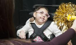 A young girl wearing glasses is gazing at a shiny pom pom.