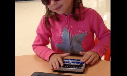 Image of a adorable four year old using iPad and refreshable braille display.
