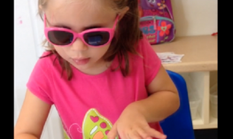 A preschooler in dark glasses swipes an iPad