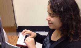 7th grade student with curly long hair using a Braille Sense U2.
