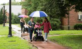 A student and her educational team head to class in the rain