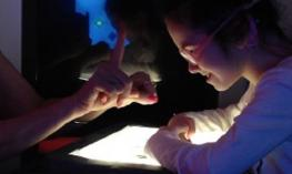 in a dim room, a student and teacher use tactile sign over a lighted tablet device