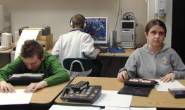 A group of student in a classroom using braille notetaker.