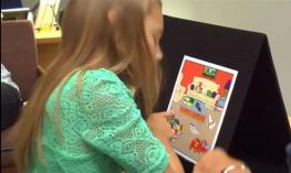 A young girl in teal shirt is pointing at an image in a picture game.