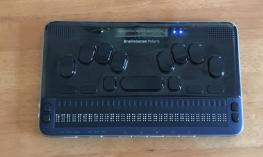 Photograph of the BrailleSense Polaris braille notetaker with a 32 cell refreshable braille display, Perkin's style keyboard.
