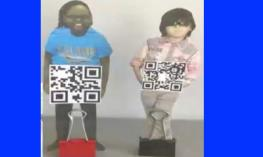 """Two QR Kids standing upright on a desk: Cutout photo of each student with hands """"holding"""" a QR code square. Binder clip at feet."""