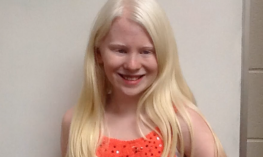 Girl long blond hair is smiling at camera